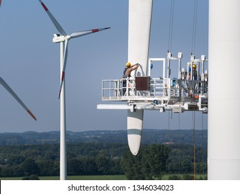 Workers on a hanging platform repair a damaged rotor blade on a wind turbine