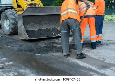 Workers on a road construction, industry and teamwork. builders workers at asphalting paver machine during Road street repairing works.