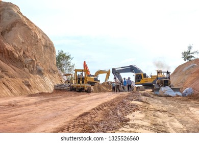 Workers on road work construction with heavy machines.