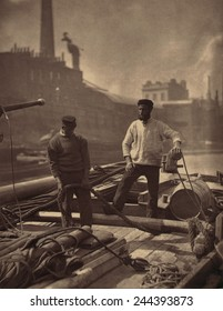 WORKERS ON THE SILENT HIGHWAY 1877 by John J. Thomson 1837-1921 shows two workmen on a barge on the Thames River England. Thomson was one of first social documentary photographers.