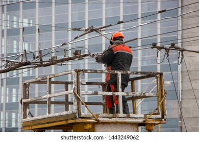 Workers on the tower repair the contact mains network for trolley buses