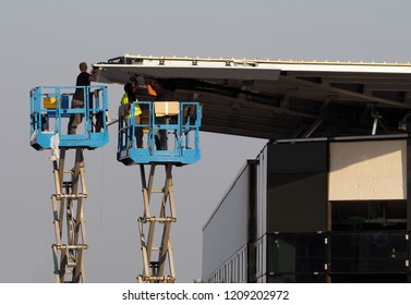 Workers on two cherry pickers, scissor lifts, finish the facade of a new building just build