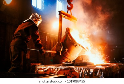 Workers operates at the metallurgical plant. The liquid metal is poured into molds. Worker controlling metal melting in furnaces.