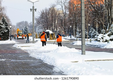 Workers in orange vests and a tractor clean the city street from fresh snow in the winter . Dnipro city, Dnepropetrovsk,   Ukraine