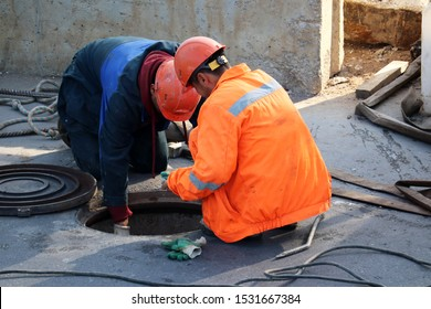 Workers over the open sewer hatch on a street. Concept of repair of sewage, underground utilities, water supply system, cable laying, water pipe accident