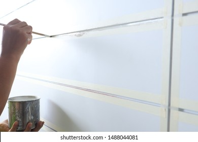 Workers are painting in the groove in the building on a white wall.