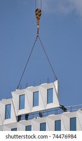 Workers positioning a hoisted prefab facade element
