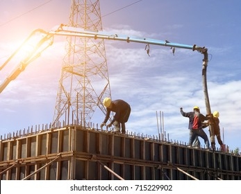 Workers are pouring concrete and have high voltage posts in the back.Light fair,selective focus.Huge concrete pump with tall arm over construction site with blue sky and clouds