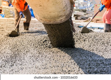 Workers pouring concrete slab for road or building.