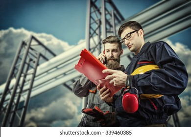 workers with protective helmet in front of industrial refinery oil pipes