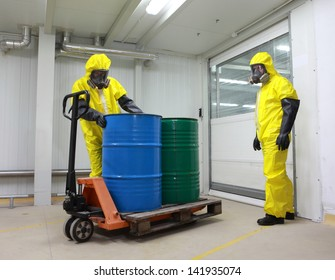 Workers in protective uniform,mask,gloves and boots working with barrels of chemicals on forklift