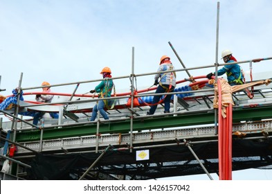 Workers pulling high voltage cable line or large electric cable which is on scaffolding the high ground and put on safety harness in in chemical plants, power plants, oil & gas industry or onshore.