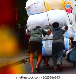 Workers are pushing a vehicle captured from the road of Kolkata, India