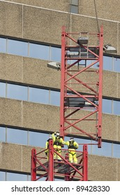 Workers reaching for a hoisted tower crane part
