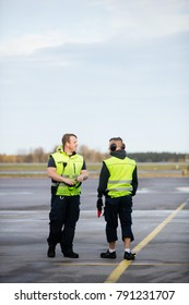Workers In Reflective Jackets Standing On Airport Runway