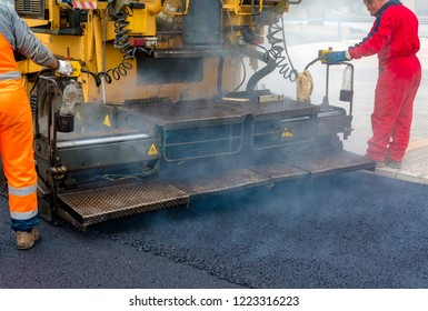 Workers regulate tracked paver laying asphalt heated to temperatures above 160 ° pavement on a runway
