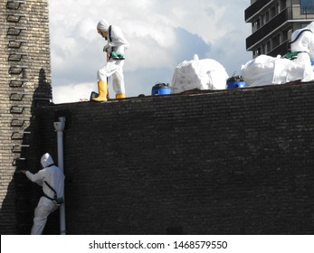 Workers remove asbestos roof. Climbing men with equipment white suit and mask on building. Protection against toxic, fibers and dust. White bags with asbestos and vacuum cleaner. Part of  serie.
