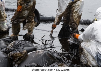 Workers remove crude oil from a beach, Crude oil on oil spill is accident  on a beach at  Ao Prao Beach, Koh Samet, Rayong, Thailand