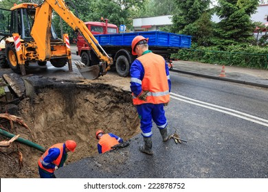 Workers repairing the damaged road - rupture of the pipeline