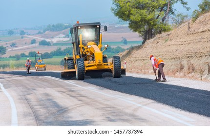 Workers repairs road under the program of planned