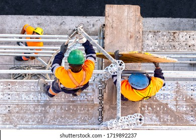 Workers seen from above setting scaffolding on a facade