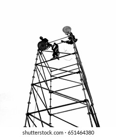 Workers set up powerful lights on scaffolds, seen in silhouette