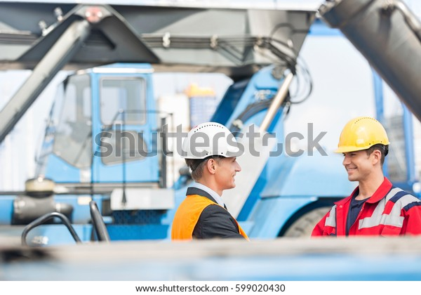 Workers shaking hands in shipping yard