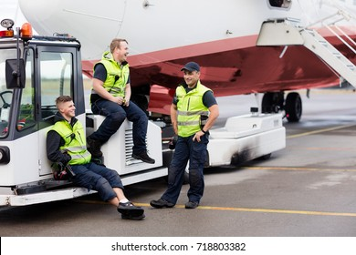 Workers Sitting On Towing Truck While Friend Standing On Runway