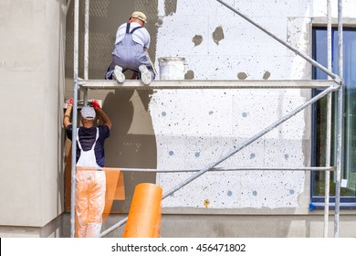 Workers spreading mortar over styrofoam insulation and mesh with trowel