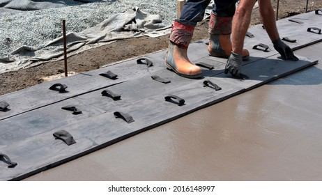 Workers stamping a concrete patio floor