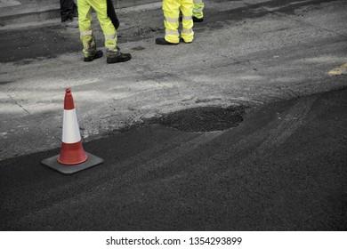 Workers at the street paving repair work.