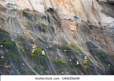 Workers strengthen the slope of the mountain with a metal mesh preventing rockfall on the road. Hondarribia, Spain. Abstract safety concept background.