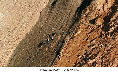 Workers strengthen the slope of the mountain with metal mesh preventing rockfall and landslide on the road, above view. workers constructing anti-landslide concrete wall prevent protect against rock