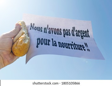 """Workers' strike. A worker holds in his hand a piece of bread and a banner, with the message """" Nous n'avons pas d'argent pour la nourriture""""- We have no money for food- in french"""