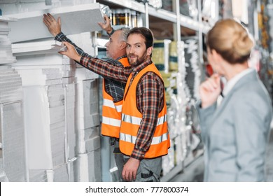 workers with styrofoam, inspector standing on on foreground in storehouse