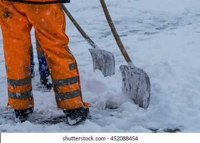 Workers sweep snow from road in winter, Cleaning road from snow storm