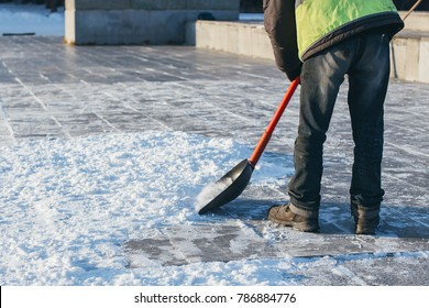 Workers sweep snow from road in winter. Cleaning road and street from snow and ice