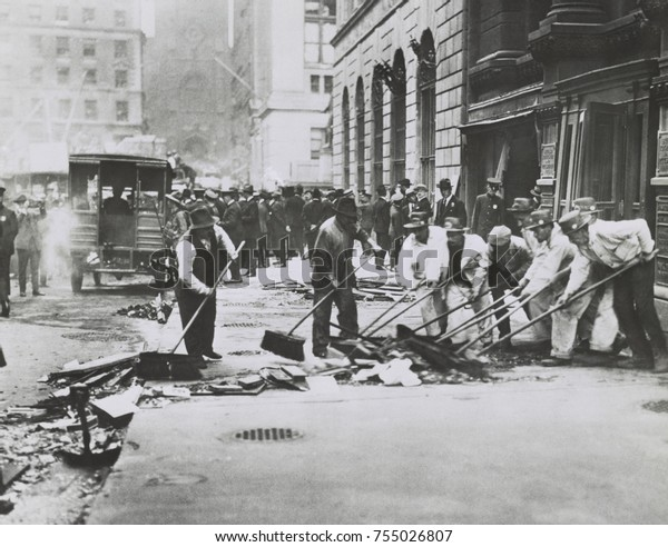 Workers sweeping up rubble and broken glass following Wall St. Bombing of Sept. 16, 1920. Within hours of the blast, the New York Stock Exchange planned to open that next day, and hired cleanup crews,