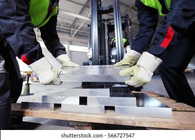Workers taking aluminium billet at CNC machine shop