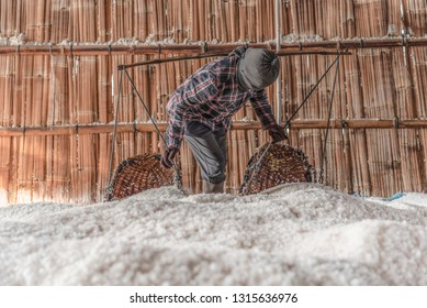 Workers with traditional shoulder pole with baskets & putting salt into warehouses