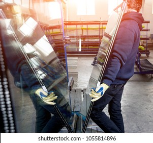 Workers transfer the glass. At the factory for the production of windows and doors of aluminum and PVC