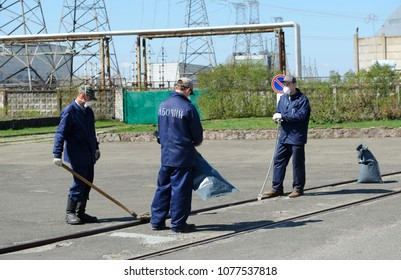 Workers in turnout coats and masks deactivating square near building of the Chernobyl Nuclear Power Plant (ChNPP). Press-tour to ChNPP for mass-media. April 20, 2018. Chernobyl, Ukraine