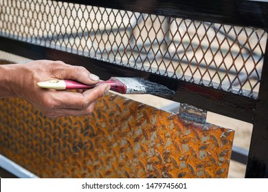 Workers use black steel paint brushes.