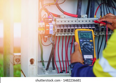 Workers use Multimeter to measure the voltage of electrical wires produced from solar energy for confirm to systems working normal.
