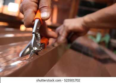 Workers use scissors to cut the metal sheet for roofing.