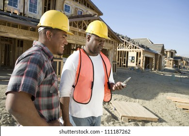 Workers using cell phone at construction site
