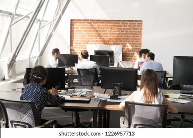 Workers using computers working at modern big open space, company staff people using pc software in coworking, busy diverse corporate employees group doing job routine in shared room office interior