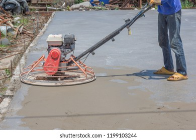 Workers are using concrete polishing machines for cement after Pouring ready-mixed concrete on steel reinforcement to make the road by mixing mobile the concrete mixer.