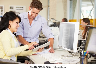 Workers Using Digital Tablet In Busy Creative Office