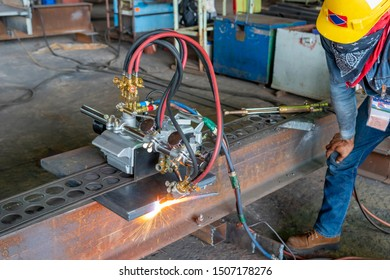 Workers are using gas cutting machines to cutting steel plates for steel structure fabrication, focus on gas cutting machines.